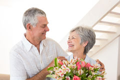 Senior couple smiling at each other holding bouquet of flowers Royalty Free Stock Image