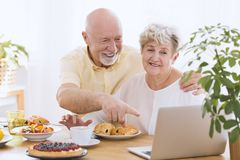 Senior couple smiling. In front of the laptop sitting at a table with cake and sweet buns royalty free stock image