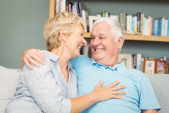 Senior couple smiling while hugging on sofa royalty free stock photo