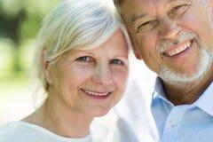 Senior couple smiling. Loving senior couple standing outdoors Royalty Free Stock Photo
