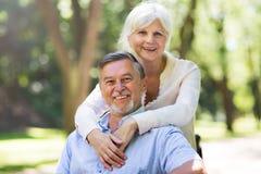 Senior couple smiling. Loving senior couple standing outdoors Royalty Free Stock Photography