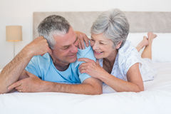 Senior couple smiling together on bed Royalty Free Stock Photo
