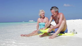 Senior Couple With Snorkels Enjoying Beach Holiday. Senior couple sitting at waters edge putting on flippers.Shot on Canon 5d Mk2 with a frame rate of 30fps stock footage