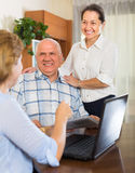 Senior couple with social worker at home Stock Photo