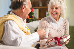 Senior couple spending Christmas together. Happy senior couple receiving presents and drinking tea while spending Christmas together Royalty Free Stock Images