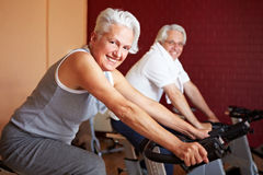 Senior couple on spinning bikes Royalty Free Stock Photography