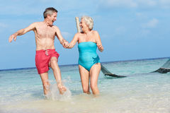 Senior Couple Splashing In Beautiful Tropical Sea Stock Photos