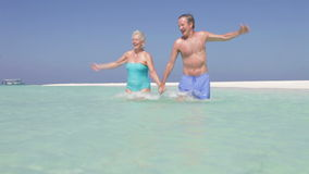Senior Couple Splashing In Beautiful Tropical Sea. Senior couple running through sea towards and past camera.Shot on Canon 5d Mk2 with a frame rate of 30fps stock footage