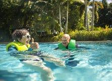 Senior couple splashing, playing, and having fun at a water park stock photo