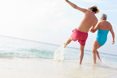 Senior Couple Splashing In Sea On Beach Holiday Royalty Free Stock Photography
