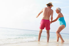 Senior Couple Splashing In Sea On Beach Holiday Stock Photography