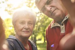 Senior couple in sports clothing holding a camera together. royalty free stock image