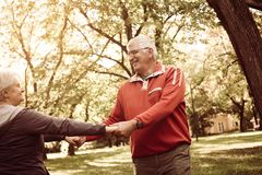 Senior couple in sports clothing holding hands and rotate in cir stock photos