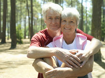 Senior couple in sportswear sitting in wood, man embracing woman, smiling, front view, portrait Royalty Free Stock Photography