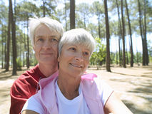 Senior couple in sportswear sitting in wood, man embracing woman, smiling, front view, portrait Royalty Free Stock Images