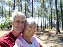 Senior couple in sportswear sitting in wood, man embracing woman, smiling, side view, portrait Royalty Free Stock Photography