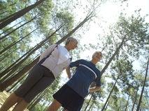 Senior couple in sportswear standing in clearing in wood, smiling, low angle view (tilt) Stock Photo