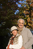 Senior couple standing in autumn garden, man embracing woman, smiling, portrait Royalty Free Stock Photo