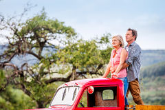 Senior couple standing in back of red pickup truck Stock Photography