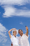 Senior couple standing on beach, man taking photograph with camera phone, smiling, low angle view Royalty Free Stock Images