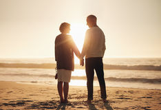 Senior couple standing on a beach together. Rear view of a senior couple holding hands on the beach. Mature couple standing together on a seashore at sunset Royalty Free Stock Image