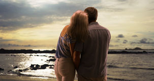 Senior couple standing at the beach watching the sunset together Royalty Free Stock Image