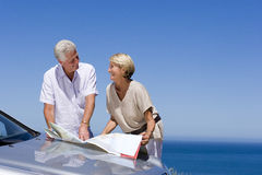 Senior couple standing beside bonnet of parked car on clifftop overlooking Atlantic Ocean, consulting map, smiling Royalty Free Stock Photos