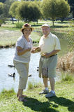 Senior Couple Standing By Duckpond Stock Photos