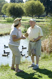 Senior Couple Standing By Duckpond Royalty Free Stock Photography