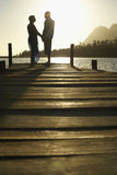 Senior Couple Standing On Edge Of Pier. Side view of happy senior couple standing on edge of pier by lake at sunset Stock Images