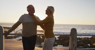 Senior couple standing in front of beach