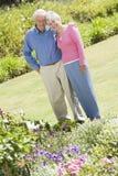 Senior couple standing in garden Stock Photo