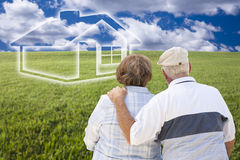 Senior Couple Standing in Grass Field Looking at Ghosted House Royalty Free Stock Images