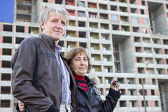 Senior couple standing with house keys in hand against apartment building Royalty Free Stock Photo