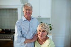Senior couple standing in kitchen. Portrait of senior couple standing in kitchen Royalty Free Stock Photo
