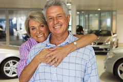 Senior couple standing in large car showroom, woman embracing man, smiling, front view, portrait Stock Image