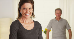 Senior couple standing in living room smiling Royalty Free Stock Image