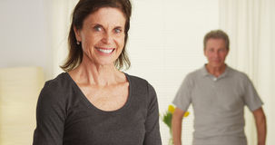 Senior couple standing in living room smiling Royalty Free Stock Photo