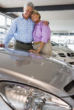 Senior couple standing beside new car in showroom, arms around each other, smiling, portrait Stock Photo