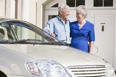 Senior couple standing next to car