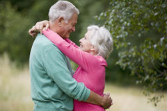 A senior couple standing outdoors, embracing Royalty Free Stock Images