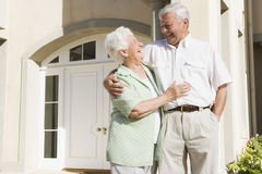 Senior couple standing outside house Royalty Free Stock Image