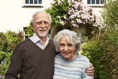 Senior Couple Standing Outside Pretty Cottage Stock Photo
