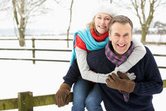 Senior Couple Standing Outside In Snowy Landscape Stock Photo
