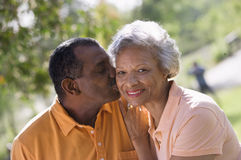 Senior couple standing in park, man kissing wife on cheek, smiling, close-up, portrait (tilt) Stock Photography