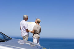 Senior couple standing beside parked car on clifftop overlooking Atlantic Ocean, consulting map, rear view Stock Images