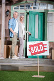 Senior couple standing on porch of new house and sold sign on green grass Royalty Free Stock Photo