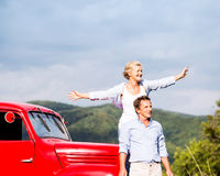 Senior couple standing at the red vintage car Stock Photos