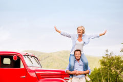 Senior couple standing at the red vintage car Stock Photography