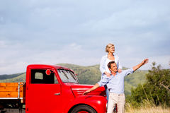 Senior couple standing at the red vintage car Royalty Free Stock Photography
